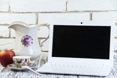 Laptop auf einem hölzernen und Ziegelsteinhintergrund Stockbild