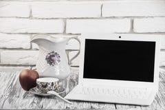 Laptop auf einem hölzernen und Ziegelsteinhintergrund Lizenzfreie Stockfotos