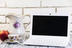 Laptop auf einem hölzernen und Ziegelsteinhintergrund Stockbilder