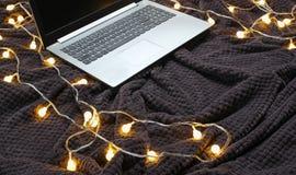 Laptop auf einer grauen Bettdecke lizenzfreie stockbilder