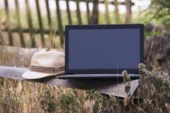 Laptop auf einer Holzbank Stockfotos