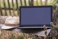 Laptop auf einer Holzbank Stockbilder