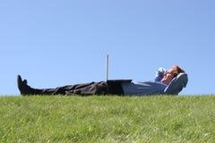 Laptop auf Geschäftsmann auf Gras Stockfotos