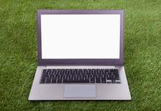 Laptop auf grünem Gras Stockfotografie