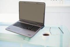 Laptop auf Schreibtisch mit Becher Kaffee und Gläsern Stockfotos