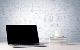 Laptop auf Schreibtisch mit Geschäftsdiagrammen auf Wand Stockbilder