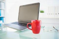 Laptop auf Schreibtisch mit rotem Becher und Gläsern Stockbilder