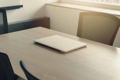 Laptop auf Tabelle im Unternehmenskonferenzsaal lizenzfreie stockfotografie