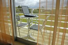 Laptop in a Balcony. A Laptop ona table outside a window with a relaxing view. Work and Leisure do Mix Royalty Free Stock Image