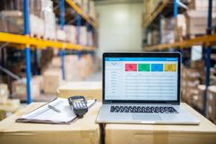 Laptop and barcode scanner on boxes in a warehouse. Laptop, barcode scanner, clipboard with notes and pen on the top of boxes in a warehouse Stock Photo