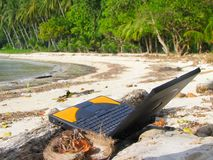 Laptop on beach. Laptop PC on tropical beach with beach debris Stock Image