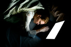 Laptop in bed. A young woman fallen asleep while working late at night with her laptop in her bed stock image