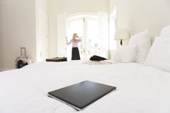Laptop on bed, woman standing by window in background Royalty Free Stock Photos