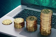 Laptop with Bitcoin logo on-screen and growing piles of golden Bitcoin Stock Images