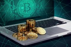 Laptop with Bitcoin symbol on-screen and piles of golden Bitcoin Stock Photo