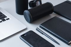 Laptop, Black phone, black notebook and black pen with black speaker on white table, close-up, office, work royalty free stock images