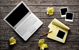 Laptop with blank instant photos and notepad Royalty Free Stock Photography