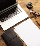The laptop, blank paper, glasses and small bell on Royalty Free Stock Images