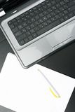Laptop and blank paper sheet on the table Stock Photography