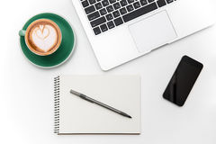 Laptop, blank screen cellphone, cup of coffee, notepad and pen. Top view of laptop, blank screen cellphone, cup of coffee, notepad and pen isolated over white Stock Photo