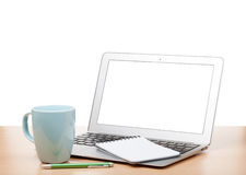 Laptop with blank screen and cup on table Royalty Free Stock Image