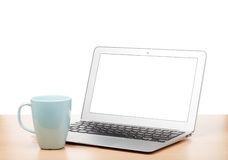 Laptop with blank screen and cup on table Royalty Free Stock Photos