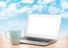 Laptop with blank screen and cup on table Stock Image