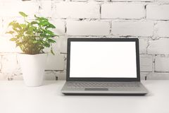 Laptop with blank screen in front of white brick wall stock photography