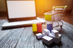 Laptop blank screen and hopping cart full of gifts with copyspace, online shopping concept.  royalty free stock photography