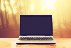 Laptop with blank screen over wooden table outdoors and blurred background of trees in the forest Royalty Free Stock Image