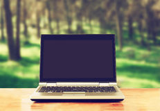 Laptop with blank screen over wooden table outdoors and blurred background of trees in the forest. Stock Images