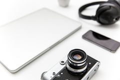 Laptop, blank screen smartphone, old camera, and headphones Stock Photo