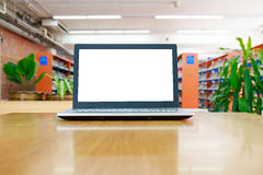 Laptop with blank screen on the table in library Royalty Free Stock Image