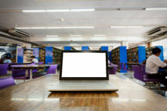 Laptop with blank screen on the table in library.  Royalty Free Stock Images