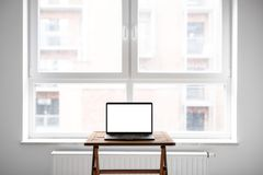 Laptop with blank screen on table in modern loft Royalty Free Stock Photos