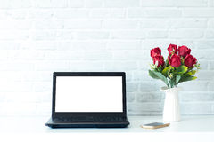 Laptop with blank screen. On white table and flower vase red color Royalty Free Stock Photography