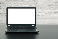 Laptop with blank screen on wooden table Stock Photo