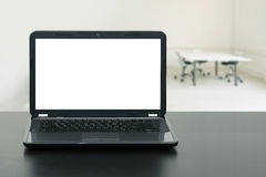 Laptop with blank screen on wooden table in the office Stock Image