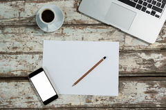 Laptop, blank sheet of paper, smartphone and coffee cup Stock Photo