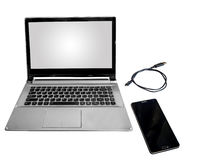 Laptop with blank white screen isolated in white with smart phone and data cable. Laptop computer blank white screen isolated in white with mobile phone and Royalty Free Stock Image