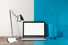 Laptop with blank white screen and lamp on table. workspace. 3d rendering. Close up of laptop with blank white screen, switched-off lamp on table. workspace. 3d stock photo