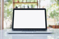 Laptop with blank white screen on marble table. Mockup image of laptop with blank white screen on marble table in modern cafe with nature background Royalty Free Stock Image