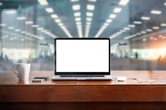 Laptop with blank white screen on table and workspace in office. Background Stock Photo
