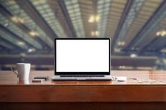 Laptop with blank white screen on table in factory background Royalty Free Stock Photos