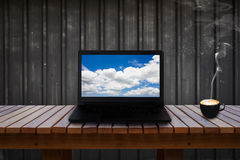 Laptop with blue sky and cloud on screen on wooden table and a cup of coffee. Stock Photography