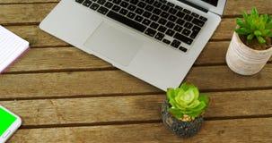 Laptop, Blumentopf, Handy, Stift und Notizblock auf Tabelle 4k stock video footage