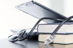 Laptop, boeken en medische stethoscoop. stock afbeeldingen