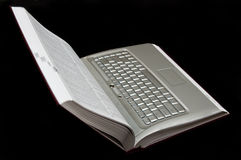 Laptop book. Concept image of open book with page of laptop keyboard isolated on black