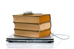 Laptop and books. Laptop on top of old books and mouse on top of the books isolated on white background Royalty Free Stock Images