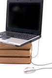 Laptop and books. Laptop on top of old books with mouse in front Royalty Free Stock Images